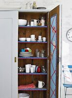 Open, wooden kitchen cupboard with crockery on shelves decorated with pretty trim