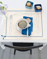A cup of coffee with biscuits on a decorative place mat with outlines of cutlery and decorative ribbon