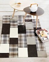 Hand-sewn patchwork rug made from squares of various monochrome fabrics