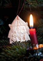 A nativty scene made of salt dough on Christmas tree with a burning candle