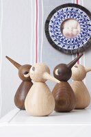 Decorative wooden birds against a wall with a picture of a cat in an ornamental picture frame
