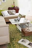 Chaise sofa and coffee table with laptop and coffee cup on green, patterned rug in living room