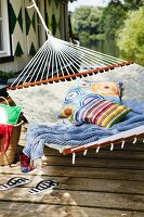 Hammock with colourful cushions & blanket outside boathouse