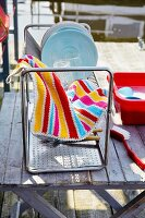 A plastic washing-up bowl, a drainer and a colourful crocheted tea towel on a wooden table outside