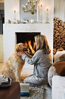 A woman with a dog in front of a fire