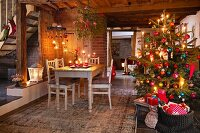 A decorated Christmas tree and a dining table in a rustic room