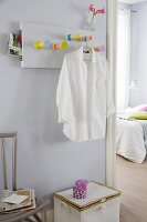 A homemade coat rack made from table legs with a white shirt on a hanger