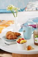 Breakfast with croissant and fruit salad on a table tray in bed