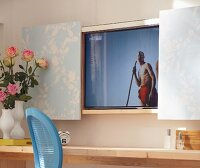 A vase of roses on a console table in front of a wall-mounted television behind wallpapered sliding doors