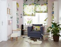 An armchair in a sunny reading corner flanked by white bookshelves and floral-and-bird-patterned folding blinds