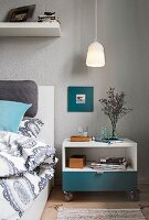A pendant lamp over a rolling bedside table next to a bed in a bedroom with grey walls