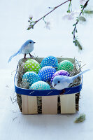 Easter eggs and decorative birds in a wooden basket
