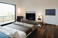 A double bed in a bedroom with dark parquet and a rustic fireplace next to floor-to-ceiling windows