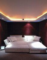 Indirektes Deckenlicht Und Spots über Breitem Sofabett In Bordeaux Farbenem  Schlafzimmer