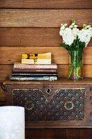 Bücher und weisse Blumen auf einer Truhe