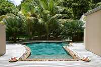 Swimming pool with wooden terrace surround in tropical garden