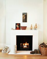 Fire in open fireplace in modernised, art collector's living room