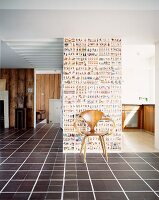 Classic wooden chair in front of wall with patterned wallpaper in open living space