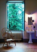 Holzstuhl vor geöffnetem Fenster im traditionellen Bad