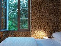 Schlafzimmer mit gold weissem Ornamentmuster auf Tapete an Wand und göffnetem Fenster
