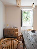 Rustikaler Tisch und Holzstühle vor offenem Fenster im Esszimmer