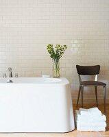 Stuhl neben freistehender Badewanne vor Wand mit weissen Fliesen