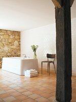 Rustikale Holzstütze im modernisierten Bad mit freistehender Badewanne