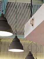 Grey, metal, industrial-style pendant lamps in front of white slatted cladding