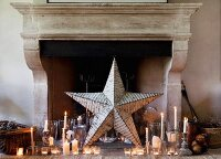 Large star and arrangement of candles in front of fireplace