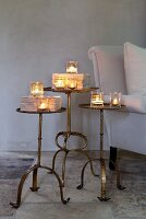 Tealight holders on antique side tables next to sofa