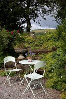 Garden table and two chairs in front of mountain landscape