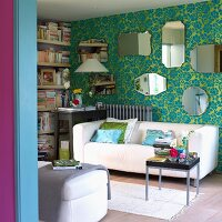 White sofa and mirrors on wall of living room with turquoise wallpaper
