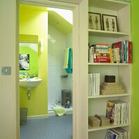 Bookcase next to open door leading to bathroom with yellow wall and light grey rubber flooring