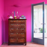 Empire-style chest of drawers against magenta wall