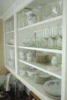Country-style glasses and crockery in white shelving unit
