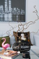 Hazelnut sprigs in an iron basket and a glass flamingo on a coffee table in a modern living room