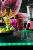 A bowl of limes next to coloured glasses and a retro blender on the illuminated frosted glass counter of a breakfast bar