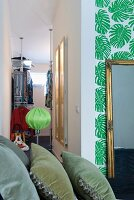 A view of a walk-in wardrobe in a bedroom featuring a multitude of styles including palm leaf wallpaper and velvet cushions in the foreground