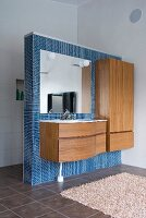 Minimalist vanity and wooden cupboard on a blue, mosaic tile dividing wall in a bathroom