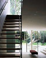 treppe mit holzstufen im offenen wohnraum und blick durch terrassenfenster auf aussentreppe. Black Bedroom Furniture Sets. Home Design Ideas