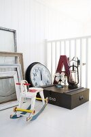 Miniature rocking horse, picture frames, wall clock, wooden crate and large letter on white surface