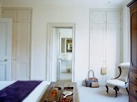 Traditional bedroom in white with floor-to-ceiling fitted wardrobes and romantic upholstered chair
