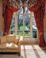 zweisitzer mit hellem satinbezug vor gerafftem vorhang mit. Black Bedroom Furniture Sets. Home Design Ideas