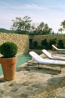 Swimming pool and sun loungers surrounded by stone wall