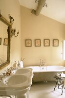 Pale bathroom with double sink and bathtub