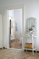 Ornate, antique, shabby chic washstand next to doorway leading to country house bedroom