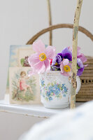 Romantic arrangement on vintage shelving - anemones in floral mug in front of nostalgic postcards