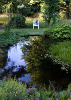 Chair with view of pond in summer garden