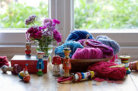 Collection of knitting dollies, wool basket and vase of sweet William in front of window