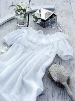 Little white dress and jewellery box on wooden surface